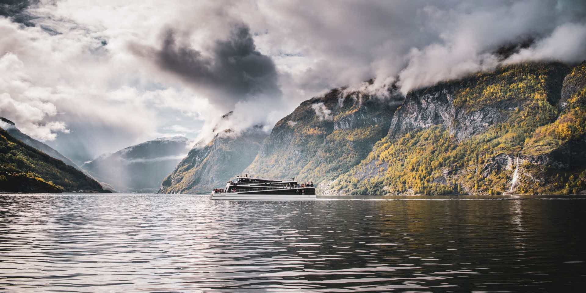 Future of The Fjords is seen in distance as sailing on cloudy and calm on the famous UNESCO Naeroyfjord in autumn