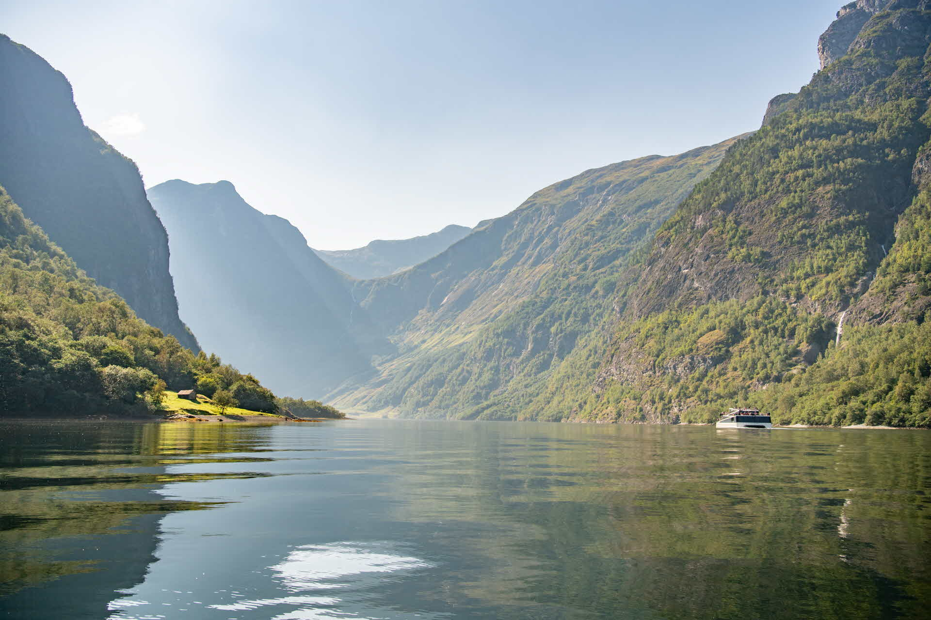 A boat sailing into the Nærøyfjord past a small farm