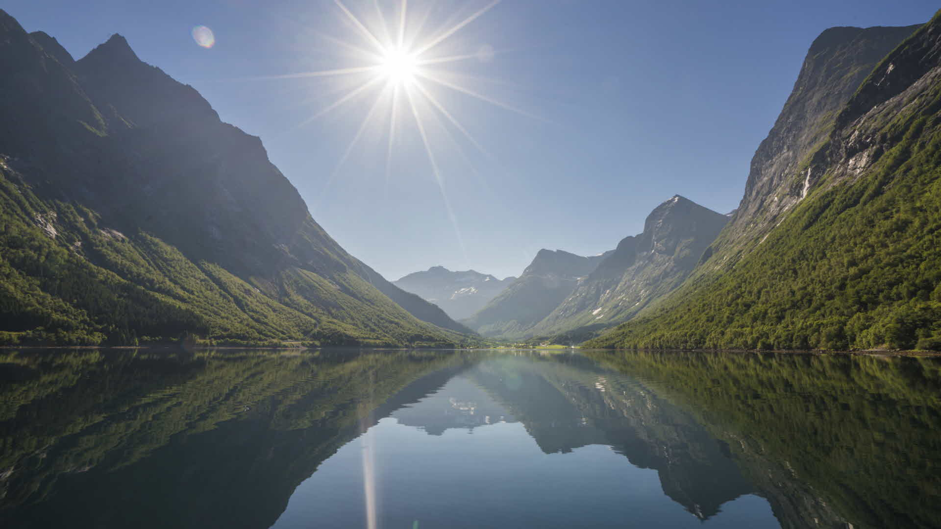 Sun flare as watching the high and dramatic peaks of the Hjorundfjord landscape is mirrored in the calm and crystal-clear sea