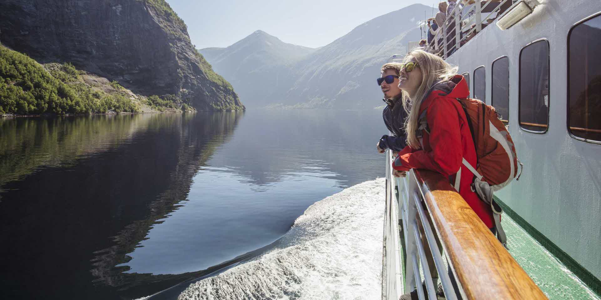 A woman and a man looking at the mountains on a fjord cruise on the Geirangerfjord