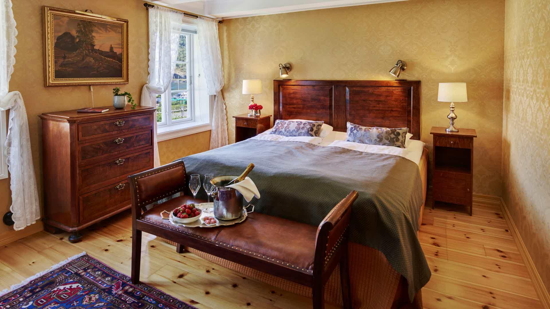 Historisk rom på Fretheim Hotel med dobbeltseng, blondegardiner og et brett med champagne og jordbær oppå en antikk benk i skinn