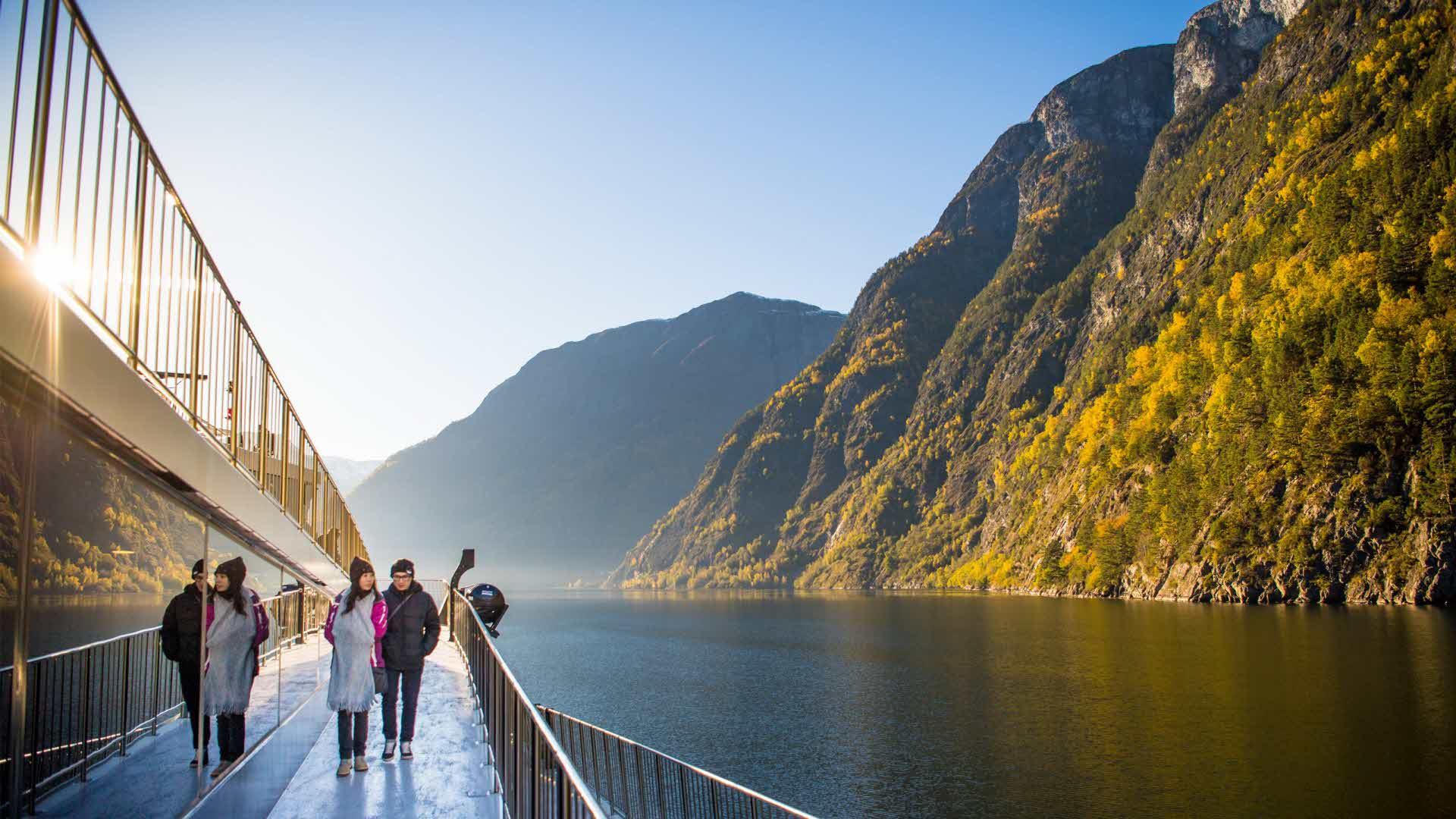 En kvinne og en mann går på utsiden av Future of The Fjords på Nærøyfjorden en fin høstdag