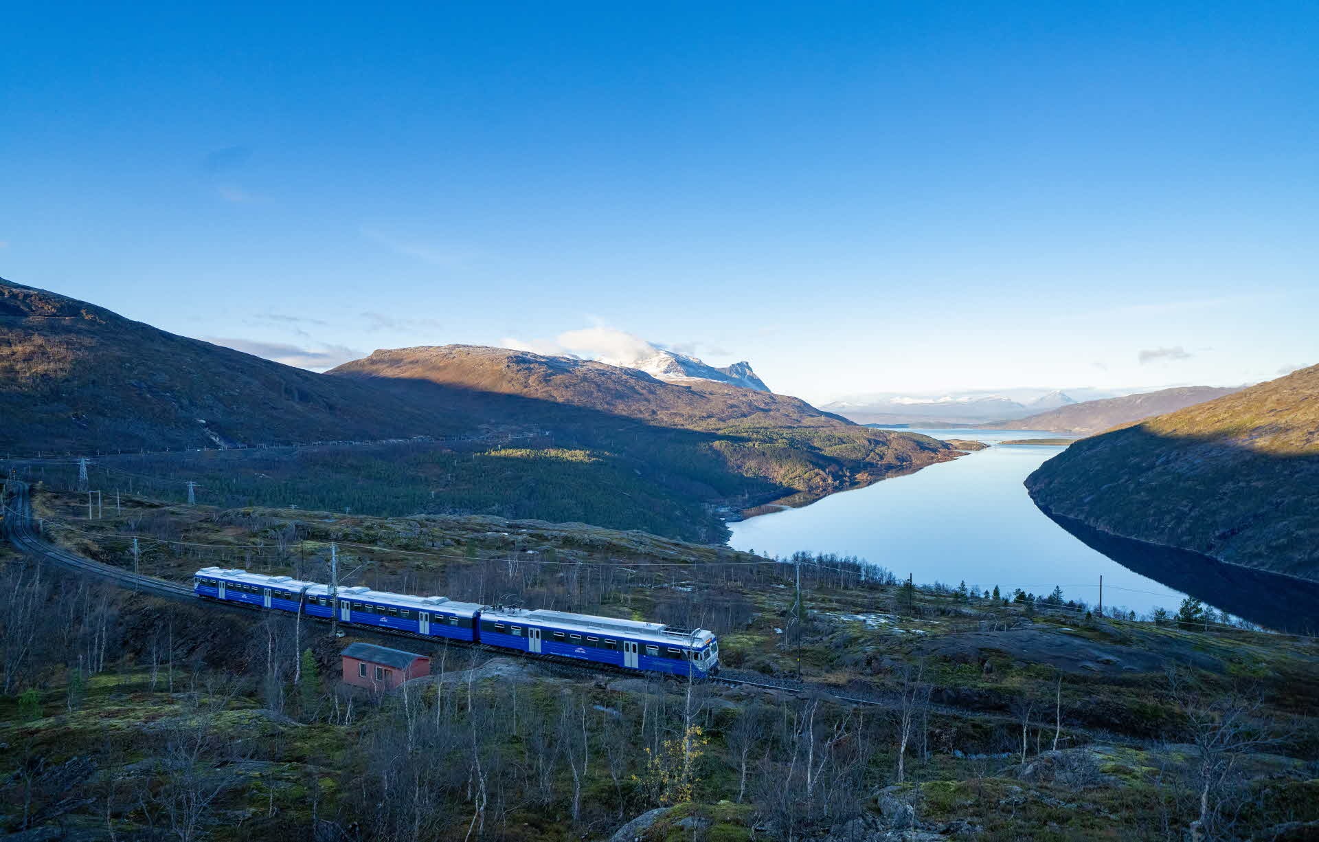 The Arctic Train passing a red little cabin on Ofot railway direction towards Narvik with Rombakfjord and mountains in background