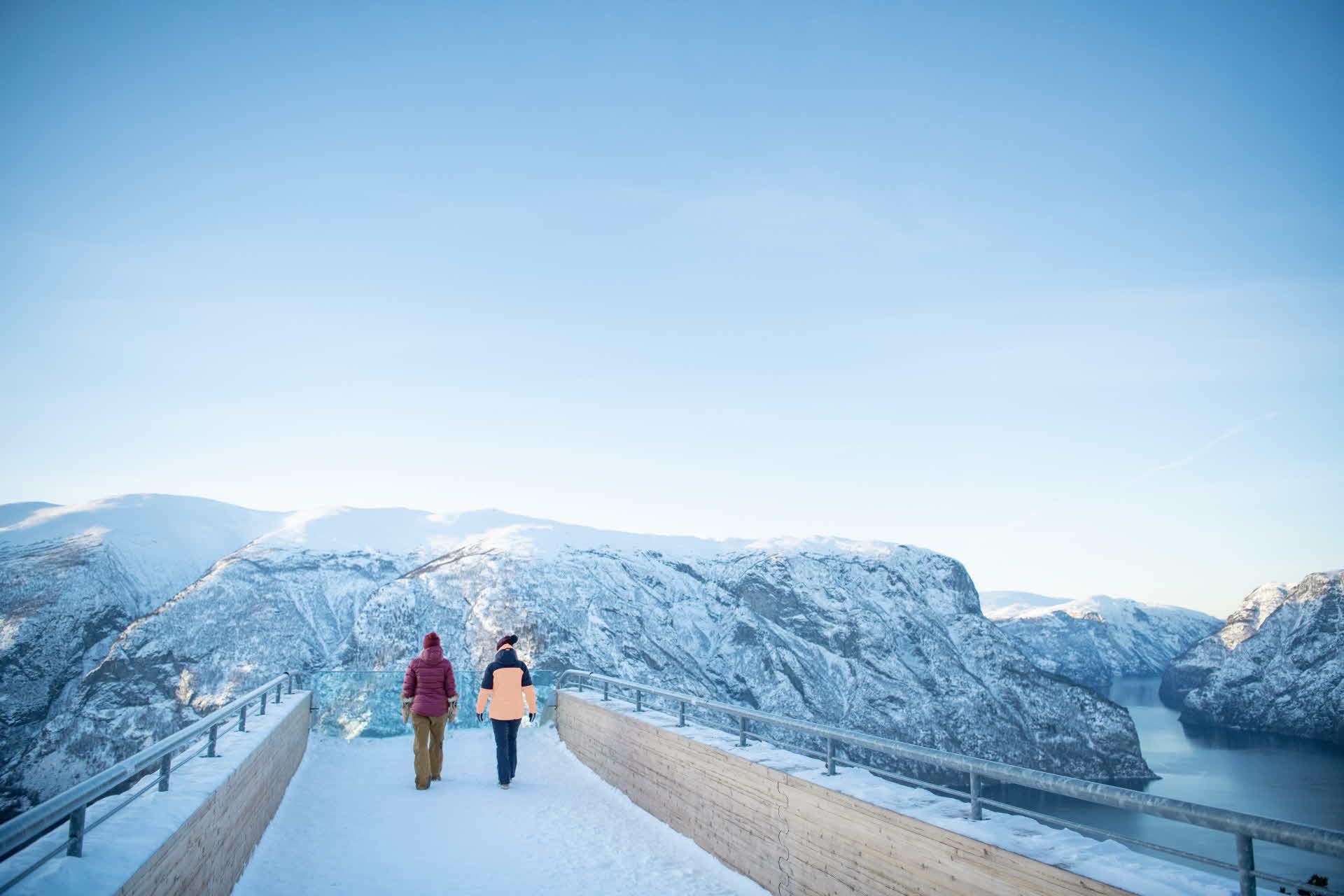 Vinter på Stegastein der to personer går utover utsiktspunktet