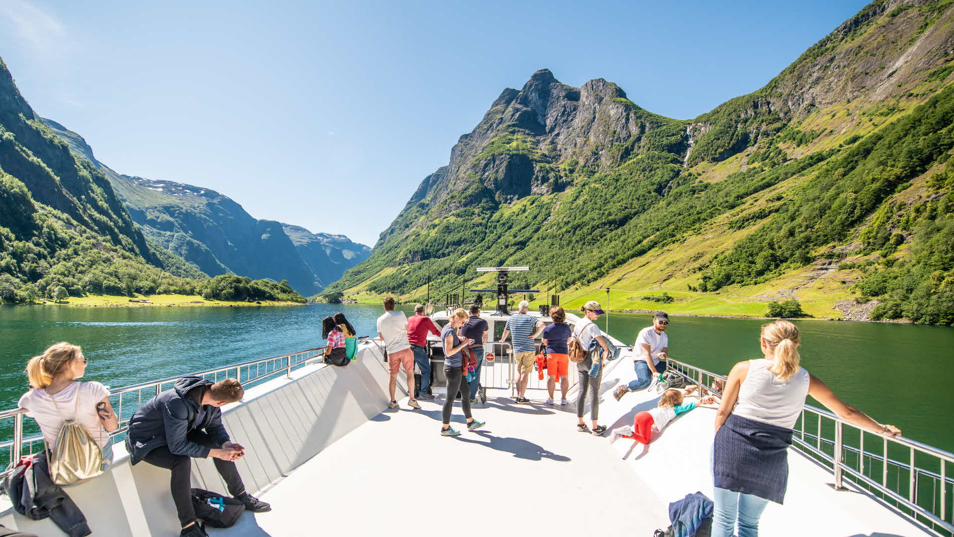 Tourists enjoying the view of Bakka from the roof of a boat on the Nærøyfjord