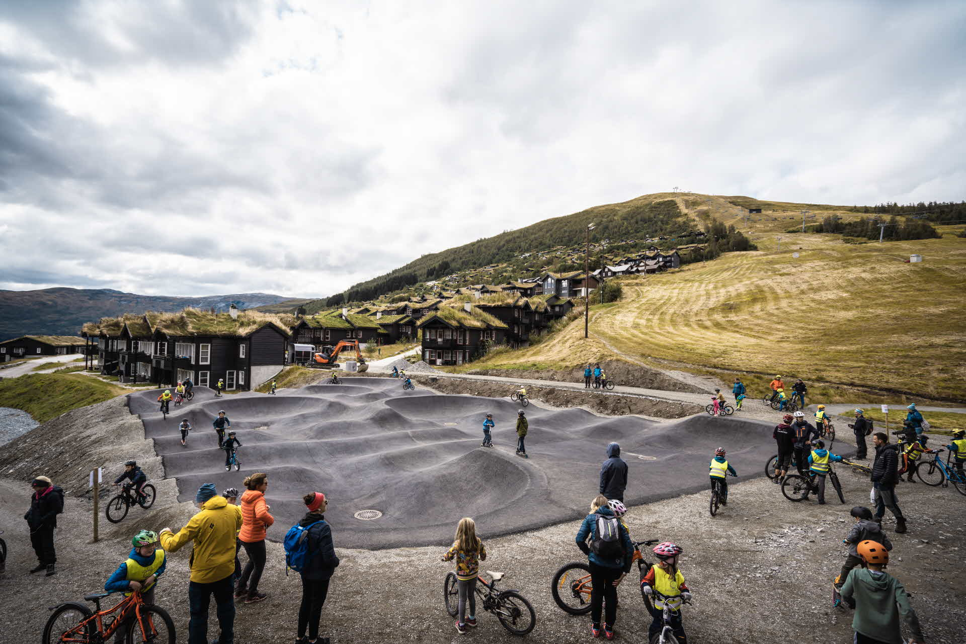 Children and adults standing round and cycling on a pumptrack in Myrkdalen Fjellandsby