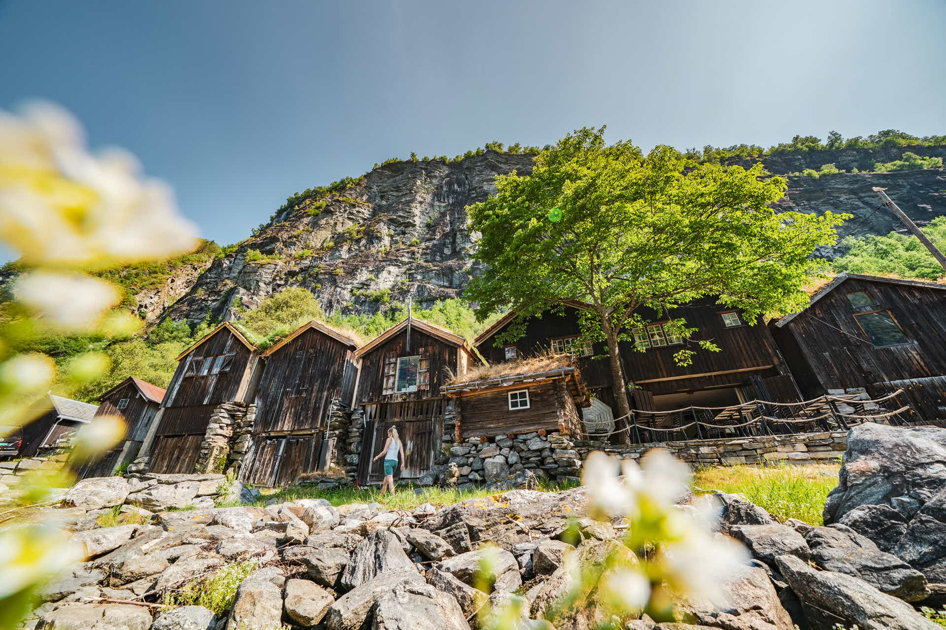 A woman walking next to old wooden houses in Geiranger