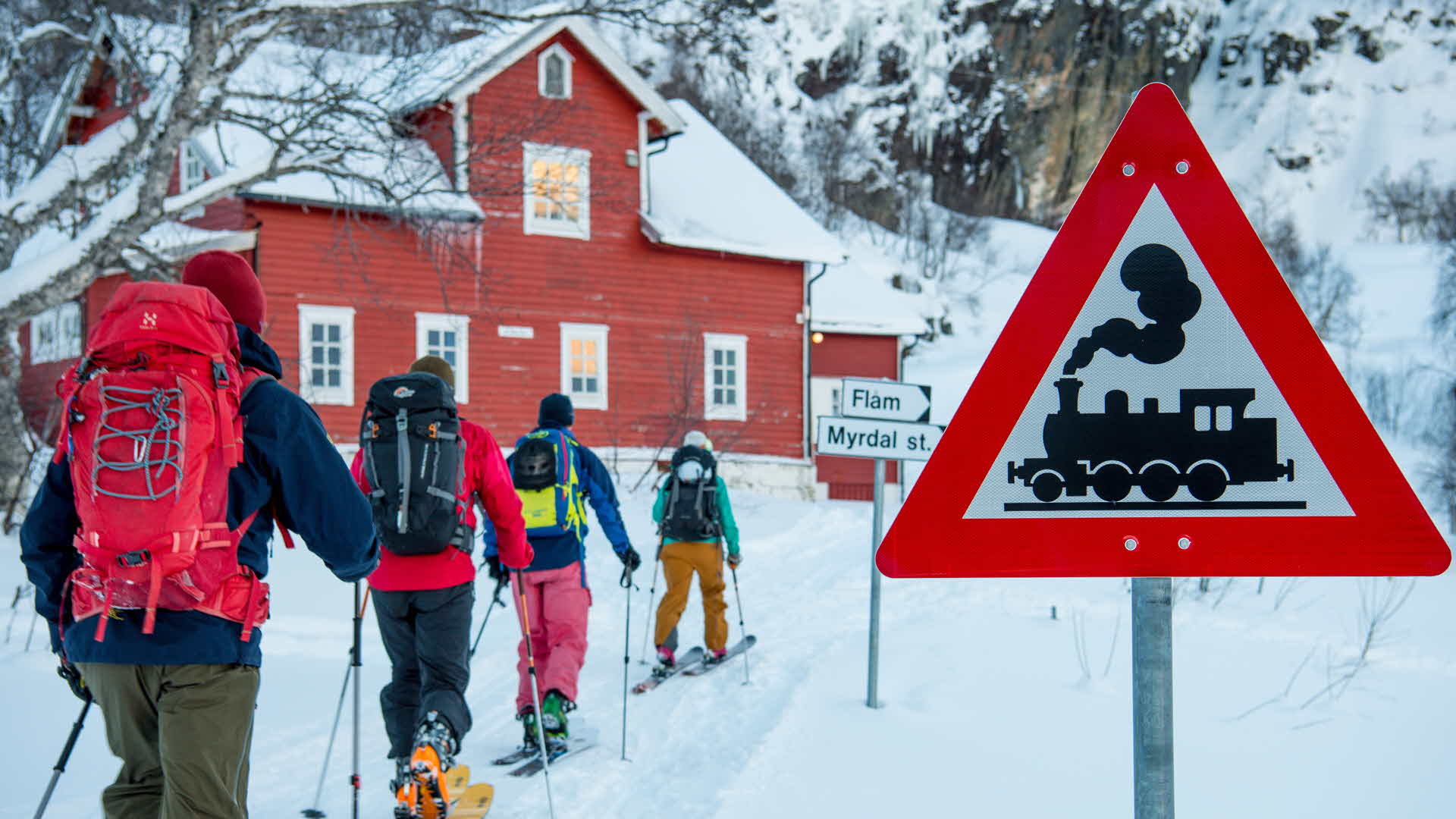 Four Randonnée skiers on their way towards red guest house at Vatnhalsen passing the flam railroad warning sign in winter